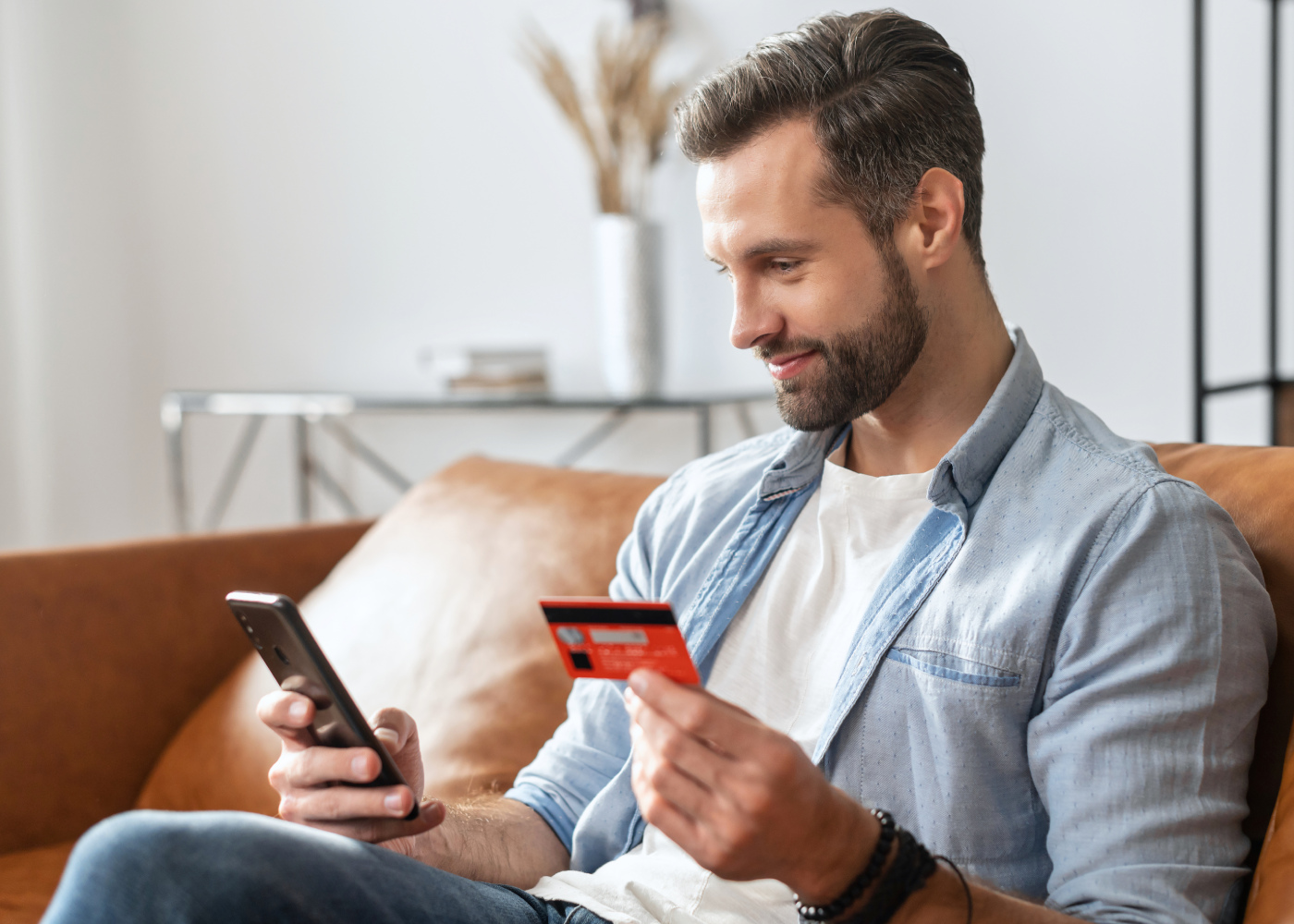 A man sitting on a brown sofa making a payment with his credit card