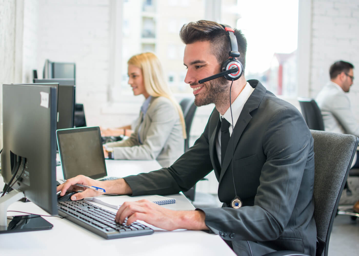 A customer service representative man wearing headphone attending the call with a smile on his face