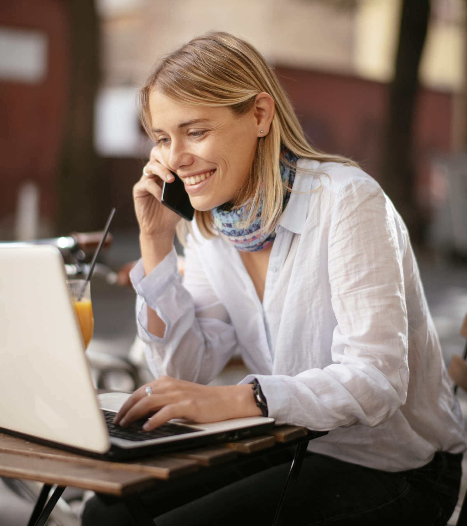 Smiling women making an online payment from mail while speaking on a call