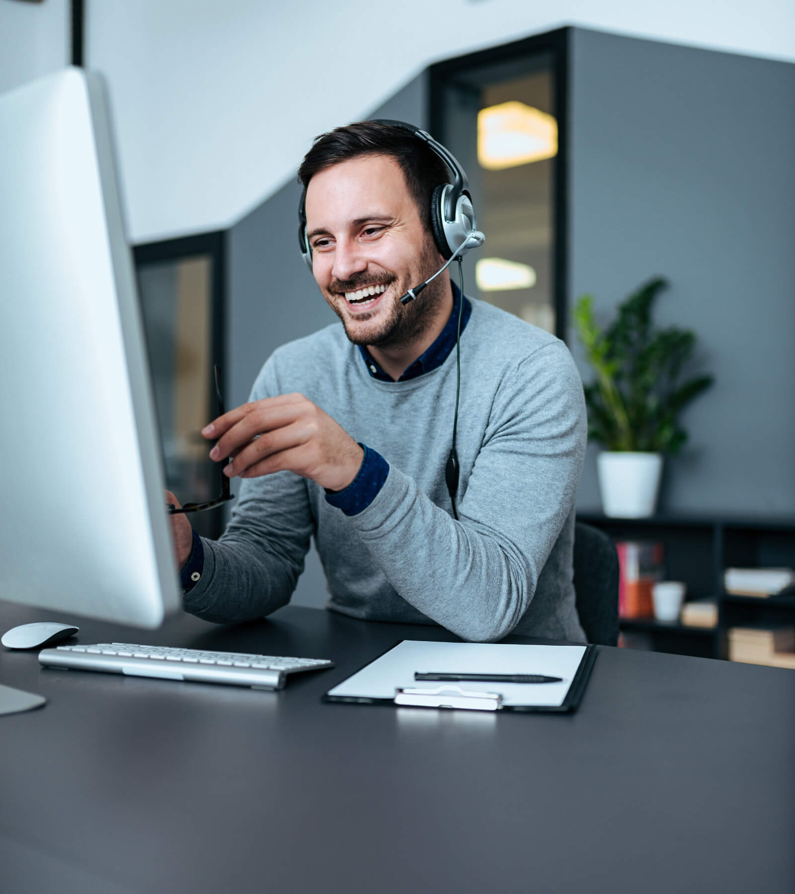A customer service representative man wearing headphone at his desk attending the call with a smile on his face
